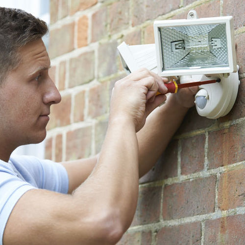 A Technician Installs Outdoor Security Lights.